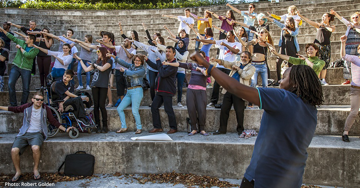 'The Complete Freedom of Truth' project in Bryanston School in Dorset, UK. A mixed group of people dance in an outdoors amphitheatric setting. Their hands are raised toward their left as they lean their bodies to the right.