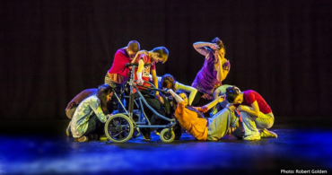 Performance for The Complete Freedom of Truth UK. 9 male and female young dancers perform on stage, against the theatre's black curtains. They create an intimate composition at the centre of the stage. Photo: Robert Golden